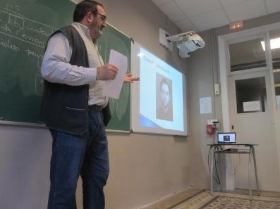 Joan Molet dando una charla en una escuela. Al fondo, una foto de Conrado Miret